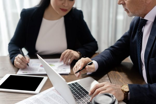 cropped view of businessman and businesswoman looking at laptop during business meeting